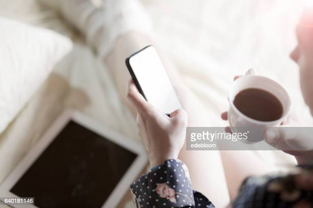 Woman using smart phone in bed
