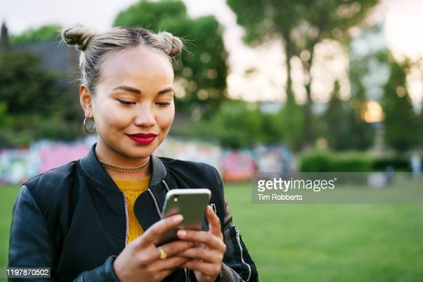 woman using smart phone in city park - youth culture stock pictures, royalty-free photos & images