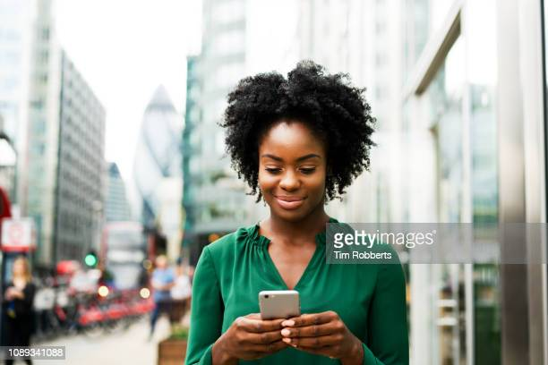 woman using smart phone in city - text messaging stock pictures, royalty-free photos & images