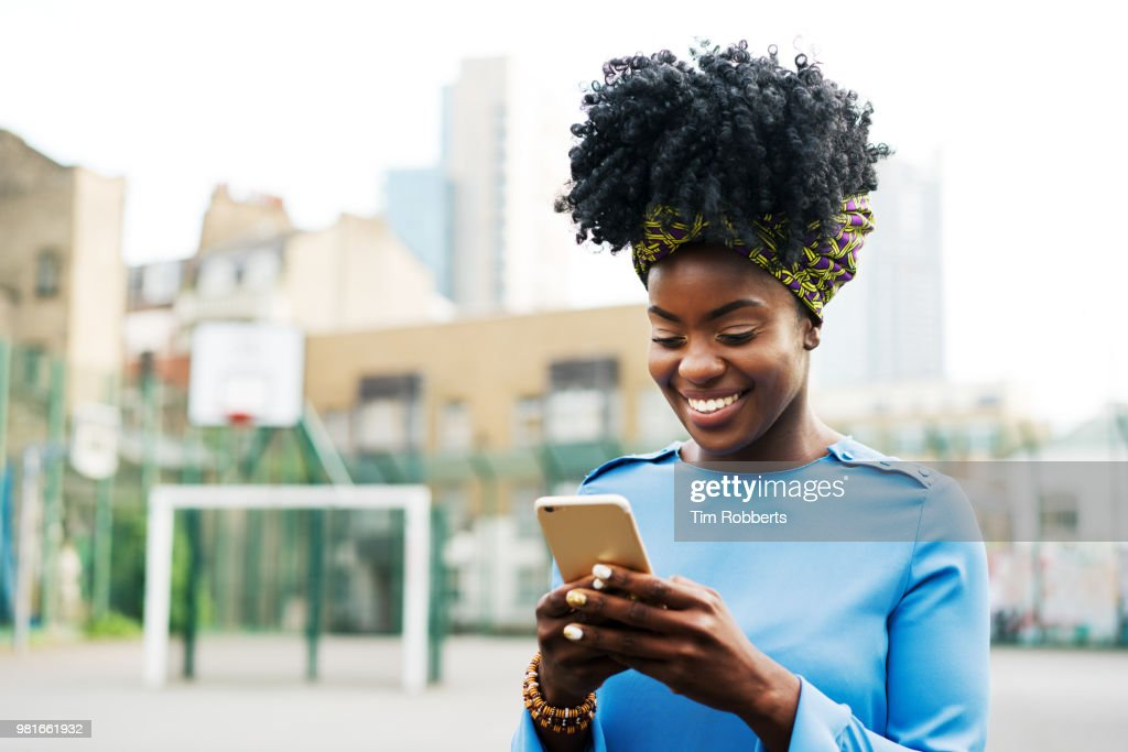 Woman using smart phone in city : Stock Photo