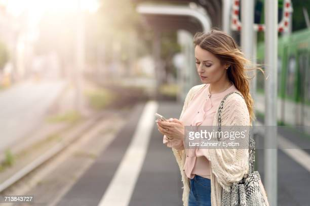 Woman Using Smart Phone In Station