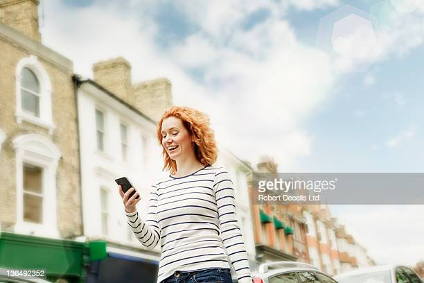 woman using smart phone in street - newpremiumuk stock pictures, royalty-free photos & images