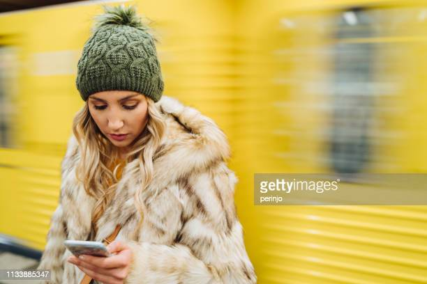 woman using smart phone in subway - incidental people stock pictures, royalty-free photos & images