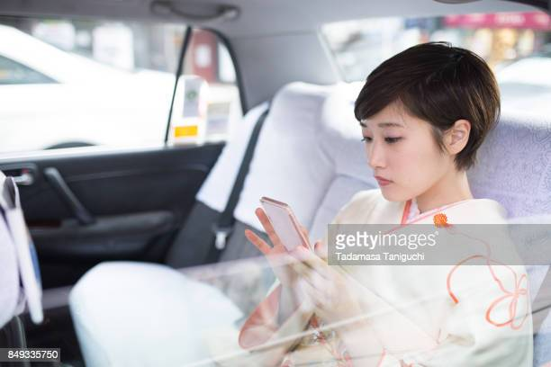 Woman using smart phone in the car
