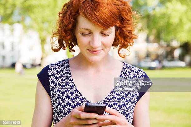 Woman using smart phone in urban park.