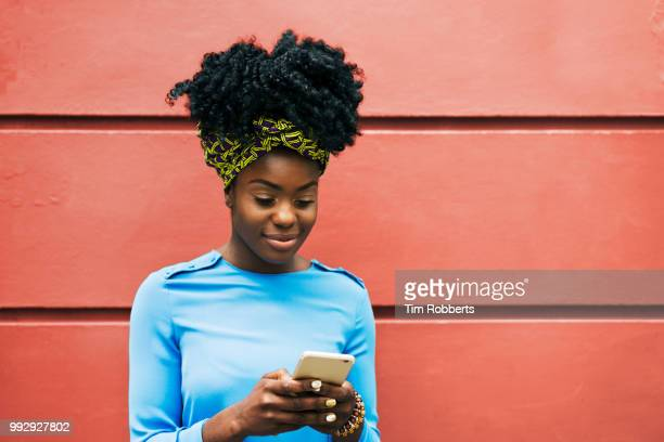 woman using smart phone infront of wall - sms'en stockfoto's en -beelden
