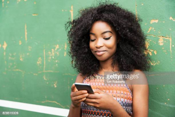 woman using smart phone next to green wall - young women stock pictures, royalty-free photos & images