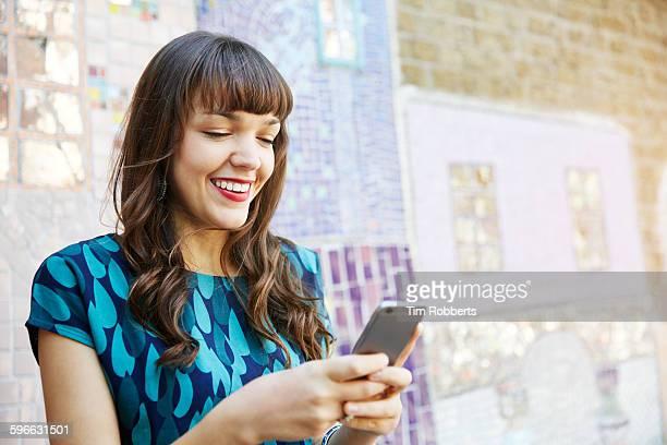 Woman using smart phone next to mosaic wall.