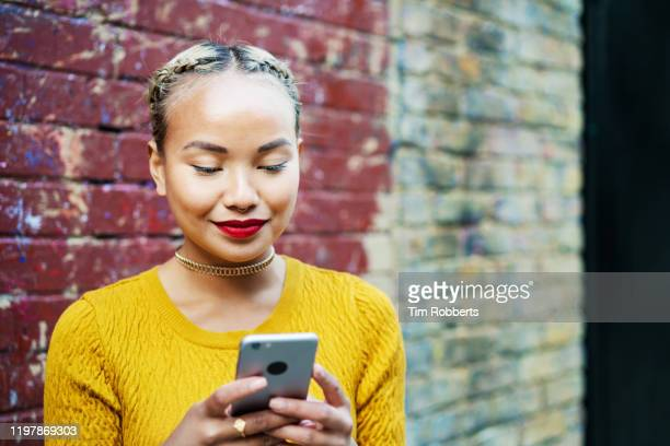 woman using smart phone, next to wall - cosmetics stock pictures, royalty-free photos & images