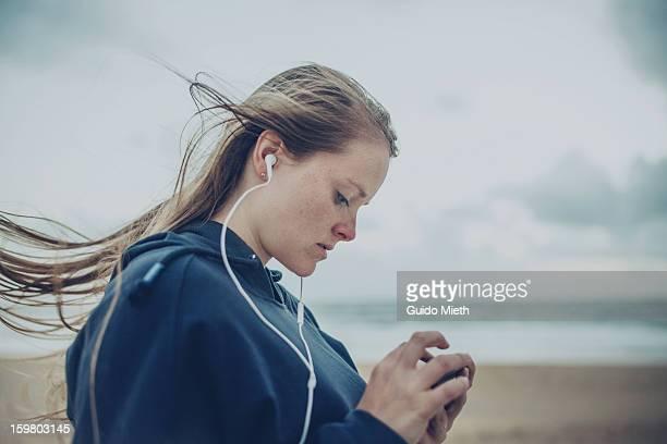 Woman using smart phone on beach.