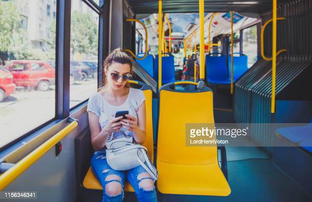 woman using smart phone on bus - seat stock pictures, royalty-free photos & images