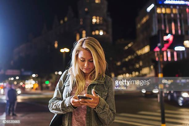 Woman using smart phone on city street at night