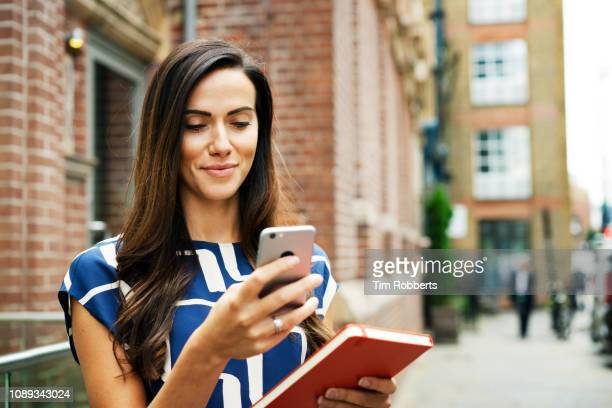 woman using smart phone on street - usare il telefono foto e immagini stock