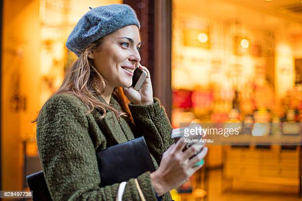 Woman using smart phone outside illuminated shop