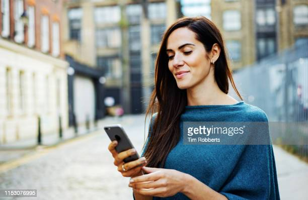 woman using smart phone outside - iphone stock pictures, royalty-free photos & images