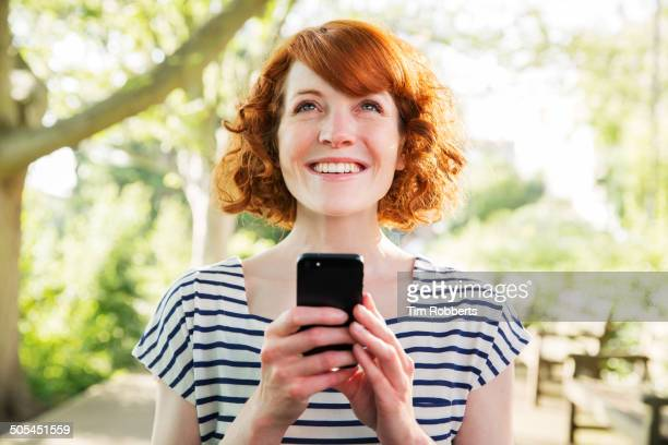 Woman using smart phone outside.