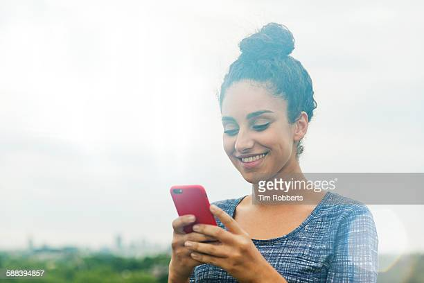 Woman using smart phone smiling.