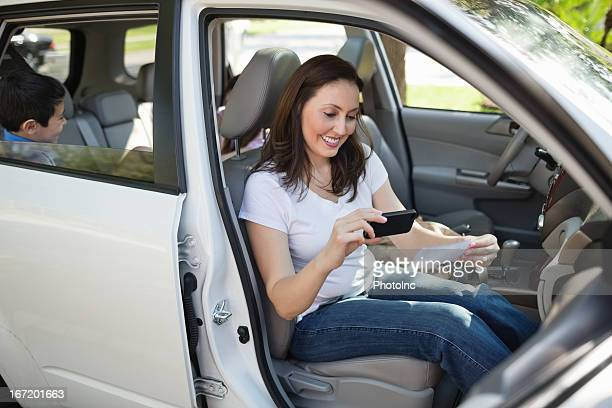Woman Using Smart Phone To Deposit Check