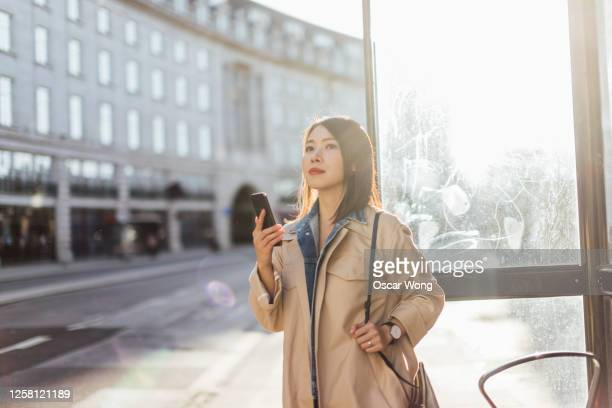 woman using smart phone, waiting for taxi in the city - waiting stock pictures, royalty-free photos & images