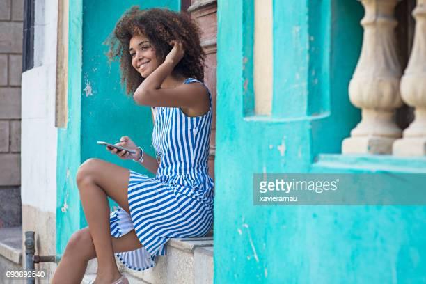 vrouw met behulp van slimme telefoon zittend bij ingang - blauwe jurk stockfoto's en -beelden