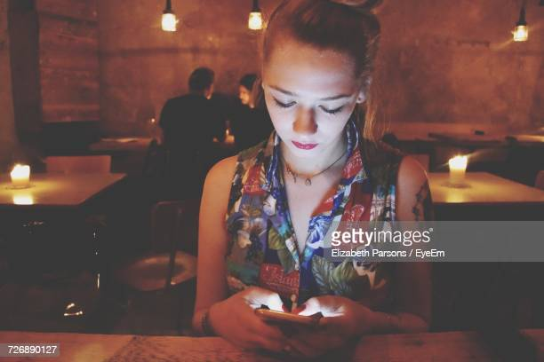 Woman Using Smart Phone While Sitting In Restaurant