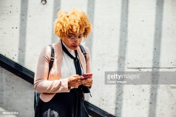 woman using smart phone while standing by wall - kroeshaar stockfoto's en -beelden