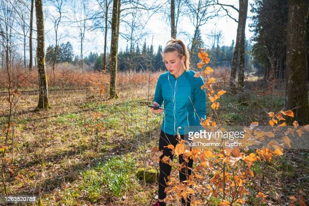 woman using smart phone while standing in forest - val thoermer stock-fotos und bilder