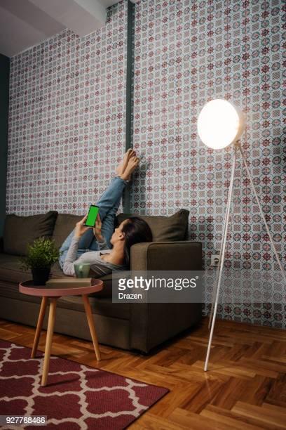 Frau mit Smartphone mit Chroma-Key-Bildschirm