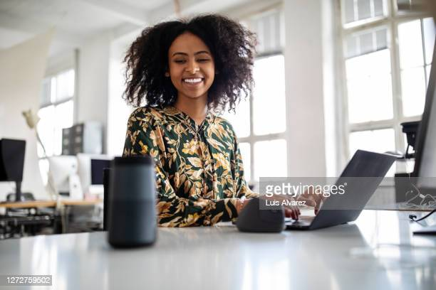 woman using smart speaker while working in office - artificial intelligence stock pictures, royalty-free photos & images