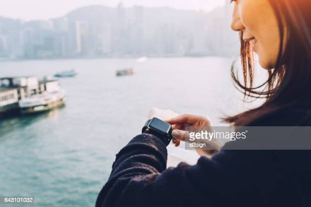 Woman using smart watch in city, standing against the cityscape of Hong Kong