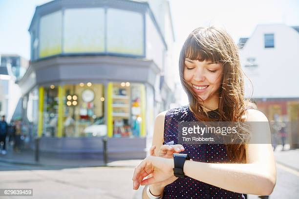 Woman using smart watch on street