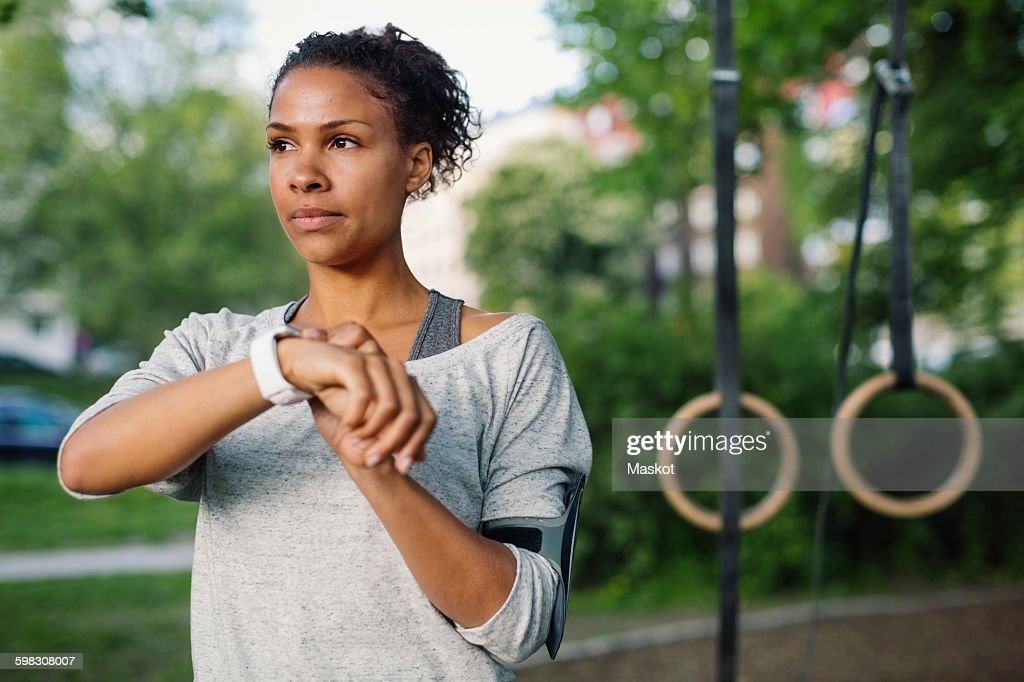 Woman using smart watch while looking away at park : Stock Photo