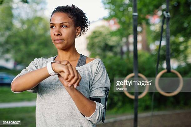 Woman using smart watch while looking away at park