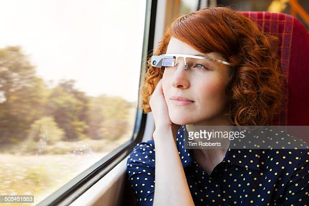Woman using Smart-Glass on train.