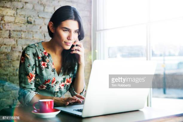 woman using smartphone and laptop in coffee shop - latin american and hispanic ethnicity stock pictures, royalty-free photos & images