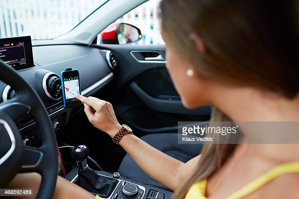Woman using smartphone as gps navigation in car