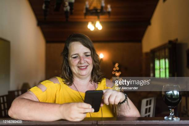 mulher usando smartphone em casa - mulheres de idade mediana - fotografias e filmes do acervo