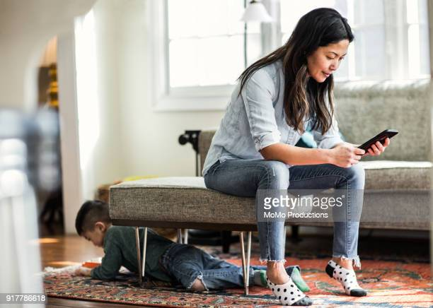 woman using smartphone at home with child in background - ringing stock pictures, royalty-free photos & images