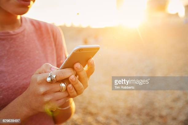 Woman using smartphone at sunset, close up