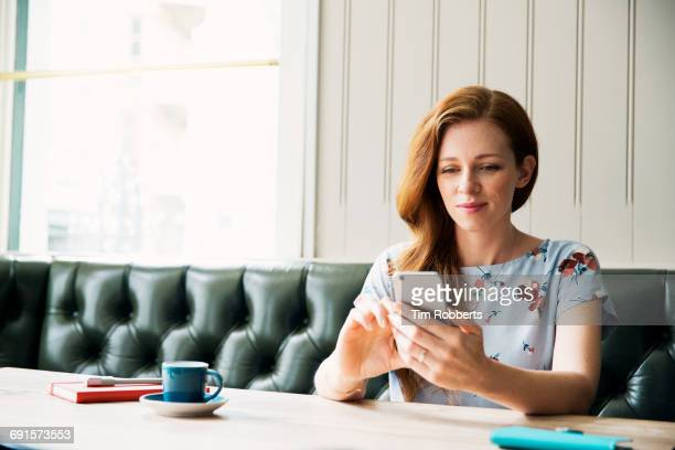 Woman using smartphone at table.