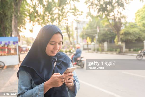 woman using smartphone by the street - indonesia stock pictures, royalty-free photos & images