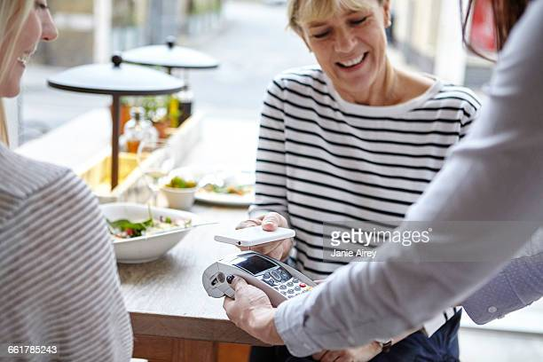 Woman using smartphone contactless payment at restaurant table, London, UK