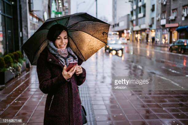 woman using smartphone downtown in rain - umbrella stock pictures, royalty-free photos & images