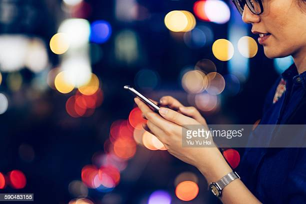 Woman using smartphone in city street at night