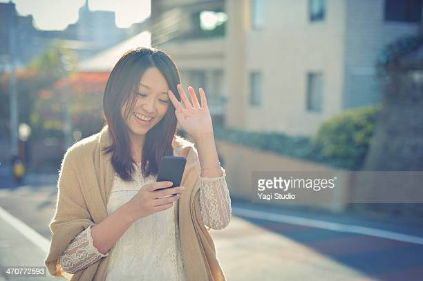 Woman using Smartphone in city street