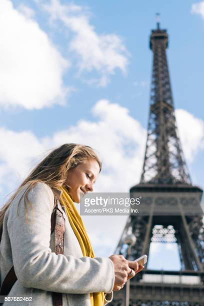 Woman using smartphone in front of the Eiffel Tower