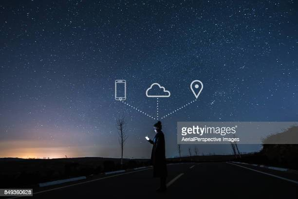 woman using smartphone in starry night - wireless technology stock pictures, royalty-free photos & images