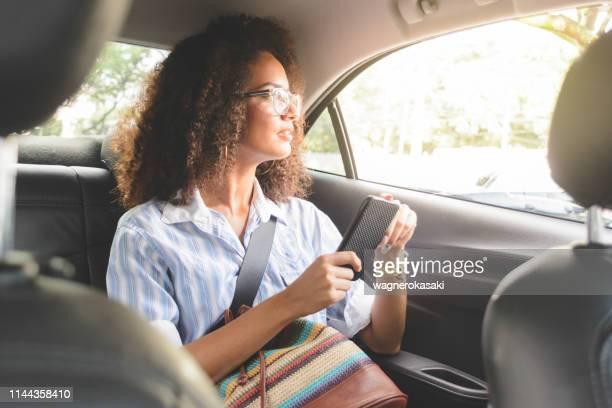 mulher que usa o smartphone no banco traseiro de um carro que olha para fora - passageiro - fotografias e filmes do acervo