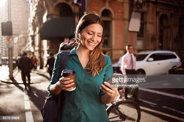Mujer usando teléfono inteligente en la ciudad