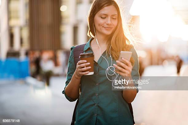 woman using smartphone in the street - ochtend stockfoto's en -beelden